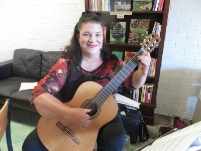 Naomi Millett playing classical guitar at Soul Tree Organic Cafe